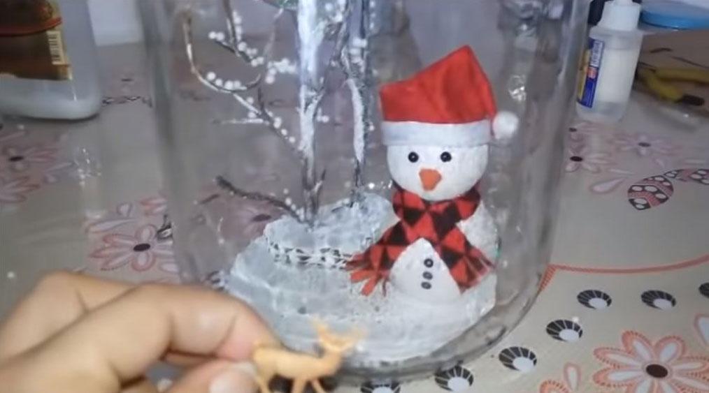 Muñeco de nieve reciclando un frasco de cristal